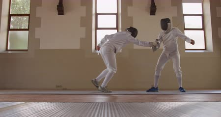 scherma : Side view of a Caucasian and a mixed race male fencer athletes during a fencing training in a gym, sparring in fencing duel wearing masks, jumping taking aim at each other with their epees, one man succeeding and taking his mask off in slow motion
