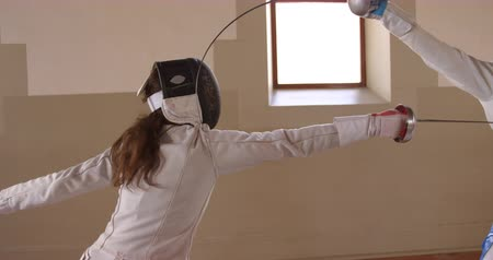 szermierka : Side view of a Caucasian and a mixed race female fencer athletes during a fencing training in a gym, sparring in fencing duel wearing masks, taking aim at each other with their epees, in slow motion