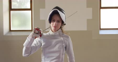 фехтование : Portrait of a happy focused Caucasian female fencer athlete during a fencing training in a gym, standing wearing glove, jacket, plastron and mask, holding an epee on her shoulder in slow motion Стоковые видеозаписи