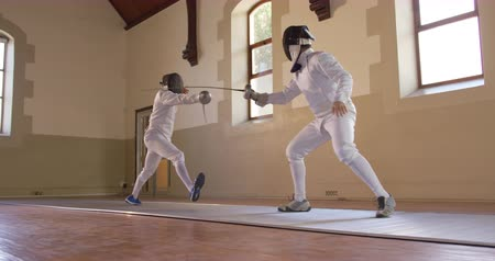 scherma : Low angle side view of a Caucasian and a mixed race male fencer athletes during a fencing training in a gym, sparring in fencing duel wearing masks, jumping taking aim at each other with their epees in slow motion