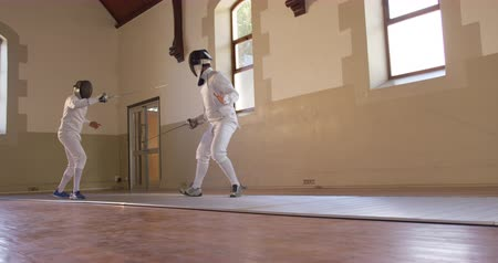 fegyelem : Low angle side view of a Caucasian and a mixed race male fencer athletes during a fencing training in a gym, sparring in fencing duel wearing masks, jumping taking aim at each other with their epees in slow motion