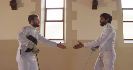 scherma : Front view of a Caucasian and a mixed race male fencer athletes during a fencing training in a gym, holding masks, smiling, shaking hands after finished fencing duel, in slow motion