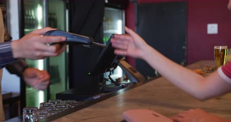 négy : Side view close up of a Caucasian woman at the bar in a pub, standing, giving credit card to a bartender, who puts it in a card reader and returns it for the female customer to key in her pin code