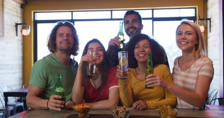 socialising : Front view of a group of five multi-ethnic male and female friends at the bar in a pub during the day, watching a sports game, holding bottles of beer and raising them to make a toast, smiling and laughing in celebration together in slow motion