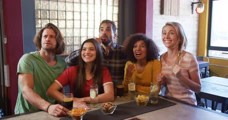 torcendo : Front view of a group of five multi-ethnic male and female friends at the bar in a pub during the day, watching a sports game, having drinks, cheering, jumping, smiling and laughing in celebration together in slow motion