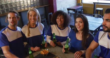 chope de bière : High angle front view of a group of five multi-ethnic male and female friends at the bar in a pub during the day, watching a sports game, holding bottles of beer and raising them to make a toast, smiling and laughing in celebration together in slow motion