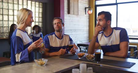 socialising : Front view of a mixed race man and a Caucasian man and a woman, sitting at the bar in a pub during the day, watching a sports game, interacting, holding glasses with beer and water in slow motion Stock Footage