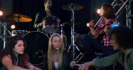 rehearsing : Front view of a group of five multi-ethnic male and female musicians having fun together before performing, one plays an acoustic guitar, one man playing drums, in slow motion
