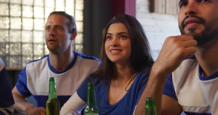 torcendo : Front view close up of a group of four multi-ethnic male and female friends at the bar in a pub during the day, watching a sports game, holding beer bottles, looking tense, cheering, in slow motion