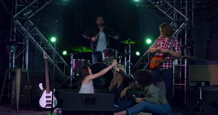 torcendo : Front view of a group of five multi-ethnic male and female musicians having fun together before performing, cheering, laughing and high fiving each other, in slow motion Vídeos