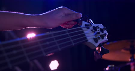 настройка : Close up detail of a mixed race female bass player rehearsing at a music venue before a performance, sitting and tuning her acoustic guitar in slow motion