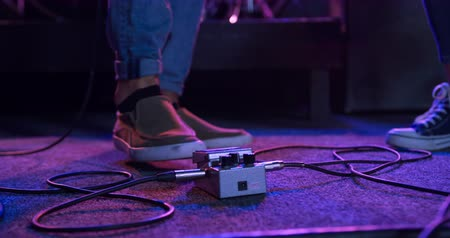 rehearsing : Front view low section detail of the foot of a guitarist playing on a spotlit stage using an effects pedal to change his guitar sound while performing with a band at a music venue, under pink lights in slow motion