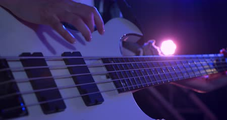 rehearsing : Close up detail of a mixed race female bass player rehearsing at a music venue before a performance, sitting and playing her white bass guitar in slow motion