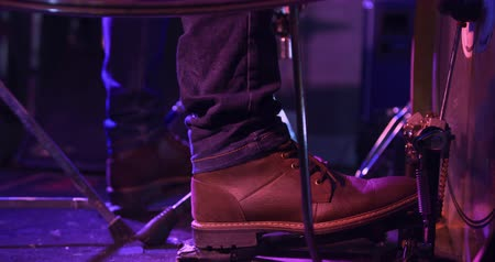 педаль : Side view low section detail of the foot of a drummer playing on a spotlit stage using a pedal to hit a drum, in slow motion