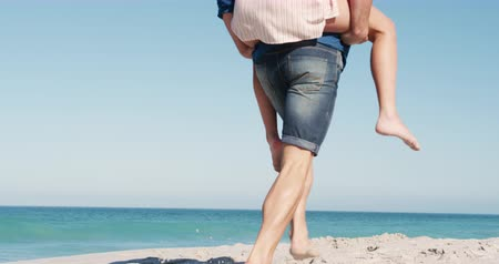 interagindo : Low angle rear view of a happy Caucasian couple in love enjoying free time on the beach together, smiling the man running and carrying the woman piggyback, smiling with blue sky and sea in the background in slow motion Vídeos