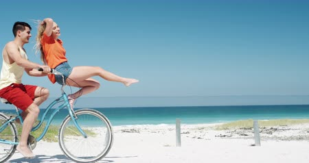 guidon : Side view of a happy Caucasian couple enjoying free time on the beach together,the man riding on a bike giving a ride to the woman sitting on the handlebar smiling with blue sky and sea in the background in slow motion