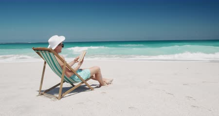 sunhat : Side view of a happy Caucasian man enjoying free time on the beach, sitting on the beach in deckchair reading a book with blue sky and sea in the background in slow motion
