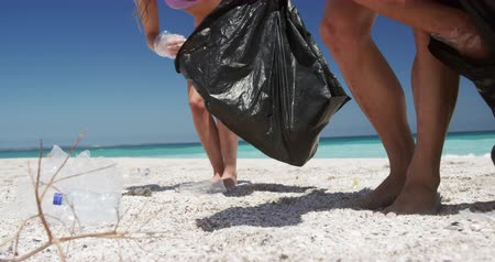 coletando : Front view of a Caucasian couple enjoying free time on the beach together, picking up rubbish and putting it into trash bags with blue sky and sea in the background in slow motion