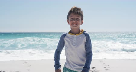 kısa : Portrait of a happy Caucasian boy enjoying free time on the beach, standing on the beach smiling to camera with blue sky and sea in the background in slow motion Stok Video