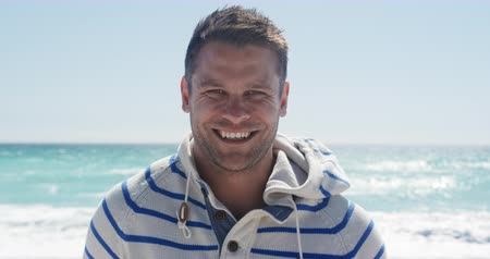 kısa : Portrait of a happy Caucasian man enjoying free time on the beach, standing on the beach smiling to camera with blue sky and sea in the background in slow motion