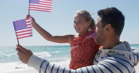 čtvrtý : Side view of a happy Caucasian man and his daughter enjoying free time on the beach together, holding American flags, man carrying the girl, smiling with blue sky and sea in the background in slow motion