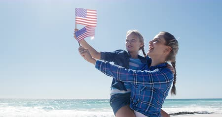 čtvrtý : Front view of a happy Caucasian woman and her daughter enjoying free time on the beach together, holding American flags, woman carrying the girl, smiling with blue sky and sea in the background in slow motion