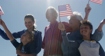 čtvrtý : Low angle front view of a multi-generation Caucasian family enjoying free time on the beach together, standing and holding American flags, smiling with blue sky in the background in slow motion