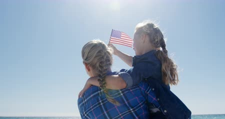 čtvrtý : Side view of a happy Caucasian woman and her daughter enjoying free time on the beach together, the girl holding American flag, woman carrying the girl with blue sky and sea in the background in slow motion Dostupné videozáznamy