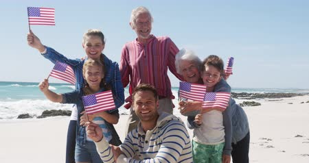 čtvrtý : Front view of a happy multi-generation Caucasian family enjoying free time on the beach together, standing and holding American flags, smiling with blue sky in the background in slow motion Dostupné videozáznamy