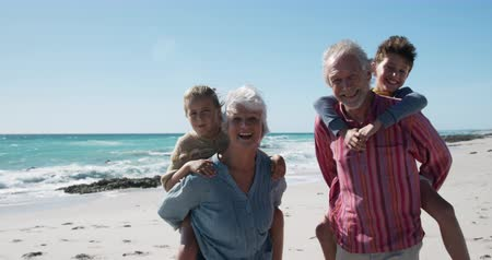 sourozenci : Portrait of a happy senior Caucasian couple and their grandson and granddaughter enjoying free time on the beach together, grandparents carrying grandchildren piggyback, smiling with sea and blue sky in the background in slow motion