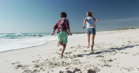 brother sister barefoot : Rear view of a Caucasian boy and girl enjoying free time on the beach together, running barefoot on sand with sea and blue sky in the background in slow motion Stockvideo