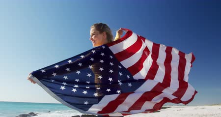 čtvrtý : Side view of a happy Caucasian woman enjoying free time on the beach, standing holding American flag smiling with blue sky and sea in the background in slow motion Dostupné videozáznamy