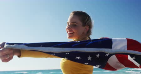 čtvrtý : Side view close up of a happy Caucasian woman enjoying free time on the beach, standing holding American flag smiling with blue sky and sea in the background in slow motion