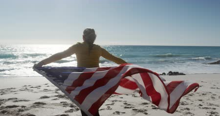 čtvrtý : Rear view of a happy Caucasian woman enjoying free time on the beach, running towards water holding American flag smiling with blue sky and sea in the background in slow motion Dostupné videozáznamy