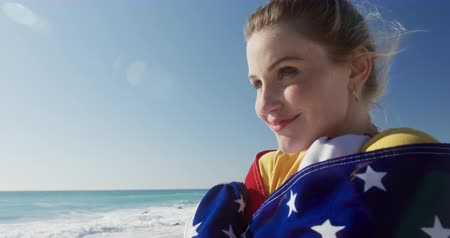 čtvrtý : Side view close up of a happy Caucasian woman enjoying free time on the beach, standing wrapped in American flag smiling with blue sky and sea in the background in slow motion