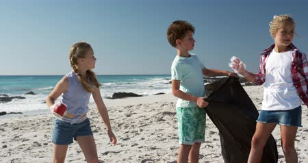 coletando : Front view of a Caucasian boy and two Caucasian girls enjoying their time on the beach together, picking up the rubbish and putting it into a trash bag with with blue sky and sea in the background