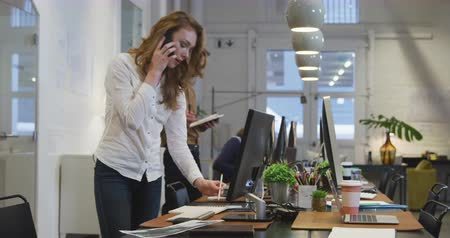 агентство : Side view of a Caucasian businesswoman working in a modern office, standing by her desk talking on her smartphone, working on a computer with her colleagues working in the background.