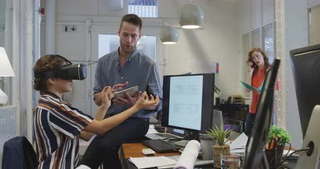 wizja : Side view of a Caucasian businessman and mixed race businesswoman working in a modern office together, the woman wearing Virtual Reality headset the man is sitting on a desk next to her holding a digital tablet with their female colleague working in the b Wideo