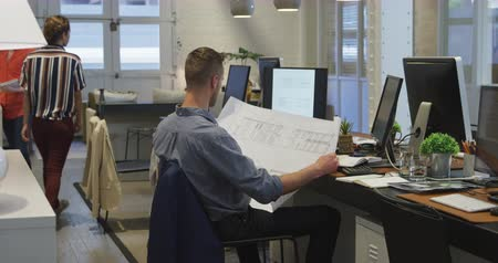 агентство : Side view of a Caucasian businessman and a businesswoman working in a modern office together, the man holding architectural drawings the woman standing by his desk talking to him with their female colleague working in the background. Стоковые видеозаписи