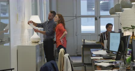 агентство : Side view of a Caucasian businessman and a businesswoman working in a modern office together, standing by a whiteboard discussing their female colleague working in the background.