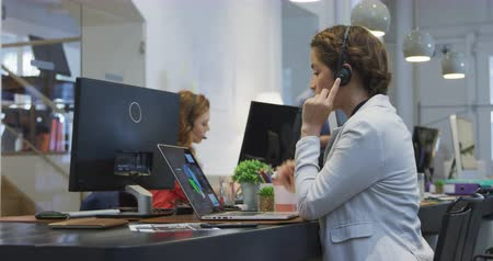 agência : Side view of a mixed race businesswoman working in a modern office, sitting at her desk wearing phone headset talking, using a digital tablet with her colleague working in the background.