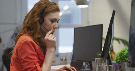 агентство : Side view of a Caucasian businesswoman working in a modern office, sitting at her desk wearing phone headset talking with her colleagues working in the background.