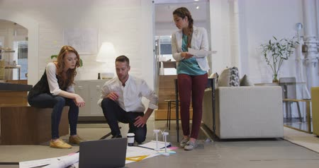 turbine : Front view of a Caucasian and mixed race businesswomen and a Caucasian businessman working in a modern office together, looking at wind turbine models, architectural plans, laptop computer on the floor, discussing brainstorming and high fiving Stock Footage