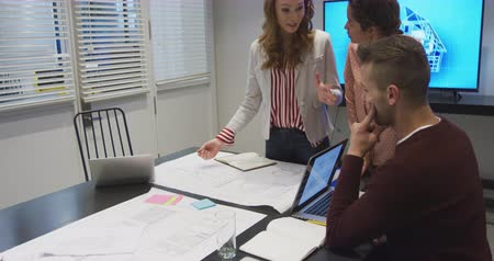 агентство : Front view of a Caucasian and mixed race businesswomen and Caucasian businessman working in a modern office together, standing by a table in a conference room, looking at architectural plans, discussing with a computer monitor showing a 3d architectural m