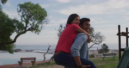 provést : Front view of a mixed race couple enjoying free time in nature on a sunny day together, the man carrying the woman piggyback in slow motion