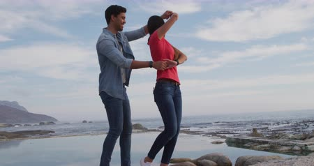 casal : Side view of a mixed race couple enjoying free time in nature on a sunny day together, dancing on a beach in slow motion Stock Footage