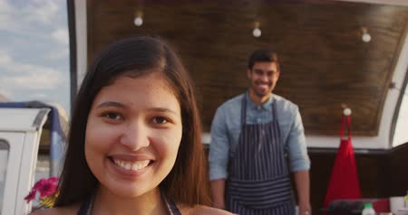 trucks : Front view of a mixed race couple standing in an food truck offering a range of takeaway food for sale, looking to camera and smiling in slow motion