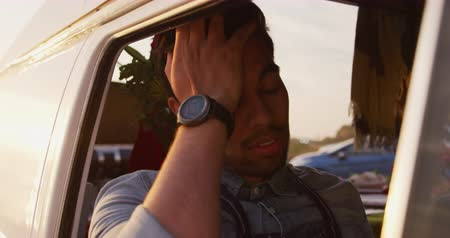 conveniente : Front view close up of a tired mixed race man sitting in food truck, resting his head on his hand in slow motion Stock Footage