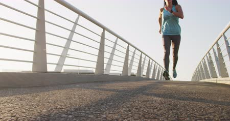corrimão : Front view of a fit Caucasian woman with long dark hair wearing sportswear, exercising outdoors in the city, running through the bridge in slow motion. Vídeos