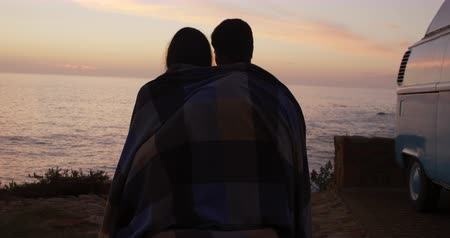 крытый : Rear view of a mixed race couple in love enjoying free time in nature together, covered in blanket, embracing, admiring the sea view in slow motion